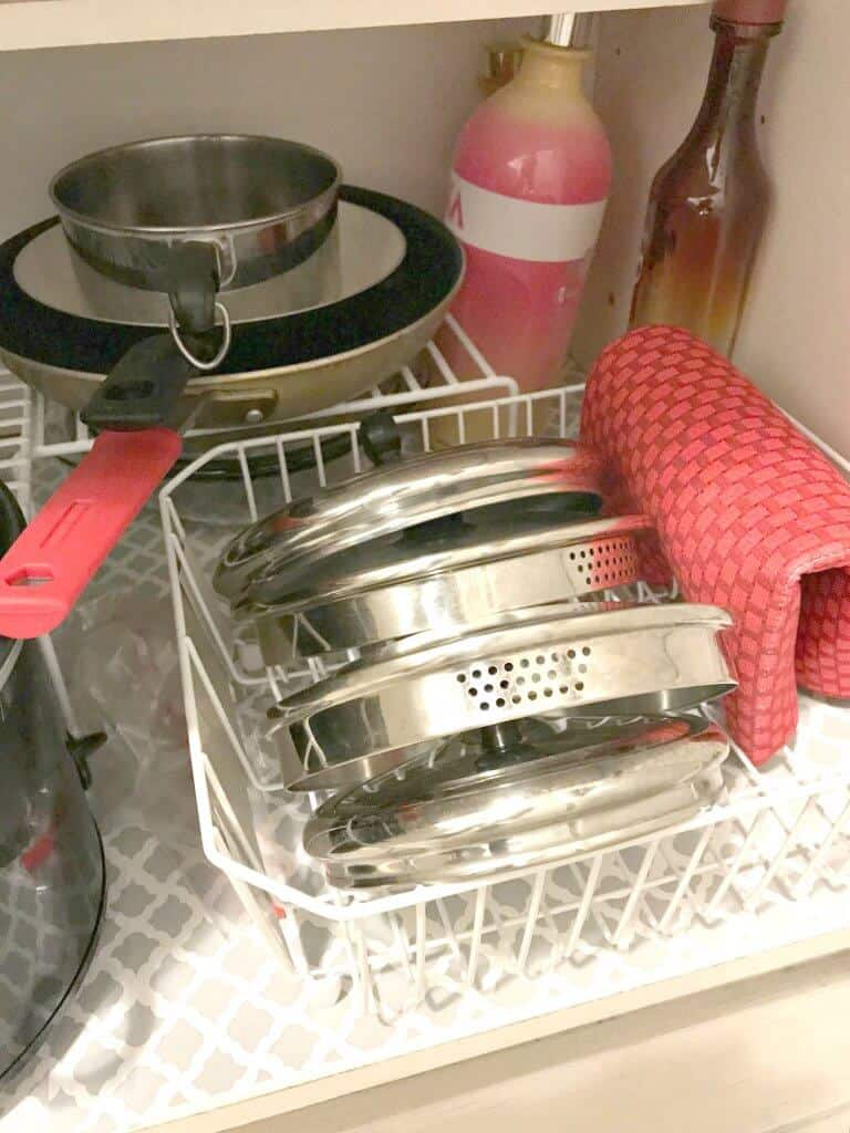 Pot lids and red towel organized in kitchen strainer with pans organized in the back of the cabinet