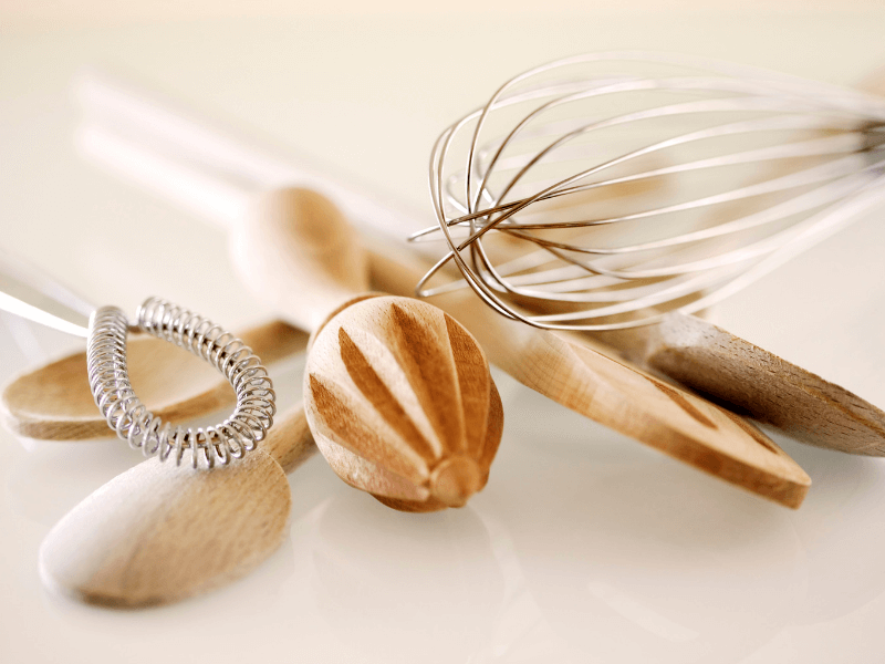 Wooden kitchen utensils and wire whisks on counter