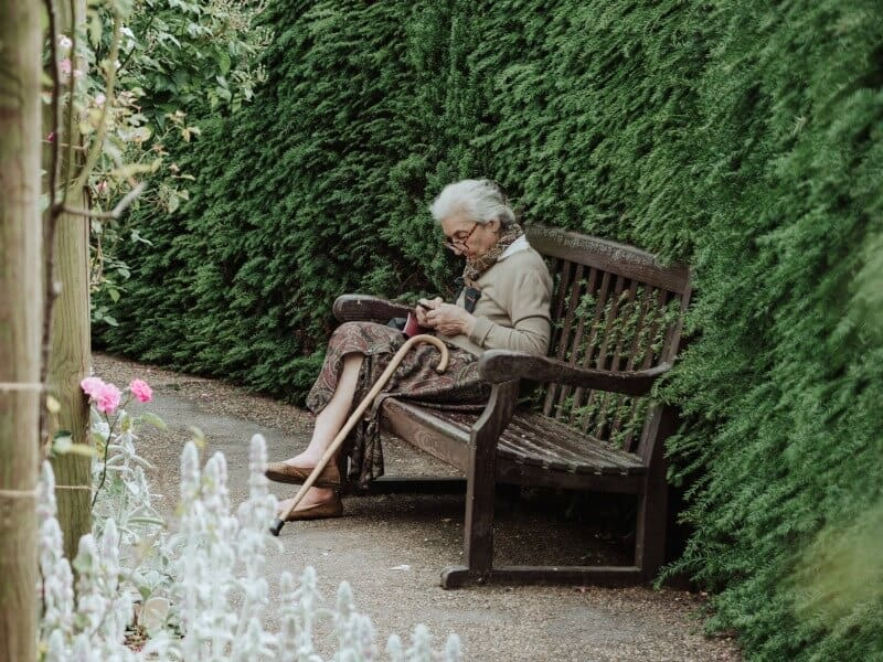 Older woman sitting alone on bench with head bowed.