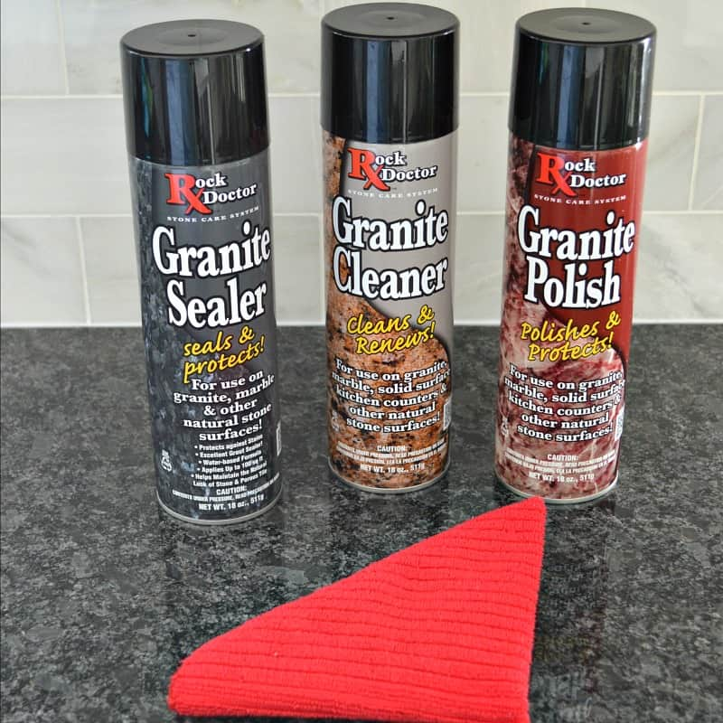 3 spray cans of granite cleaner on black counter top with white marble backsplash