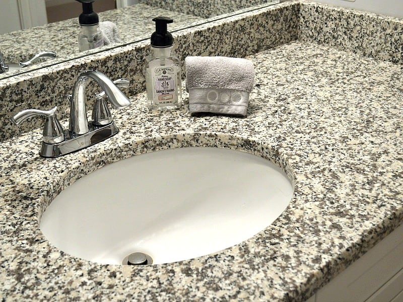 grey and white speckled bathroom counter with grey folded towel and bottle of soap