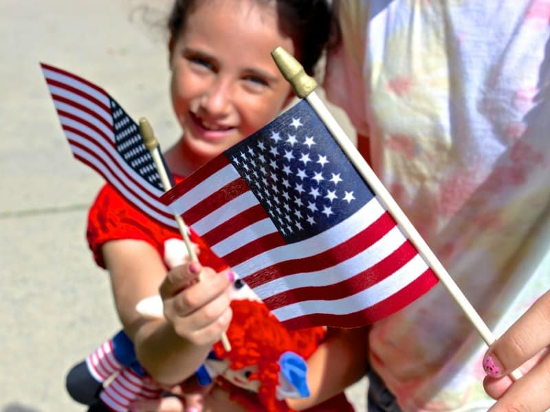 girl holding US flag and looking at camera with another flag in foreground