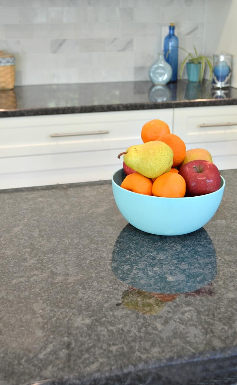 blue bowl of fruit on black countertop in kitchen