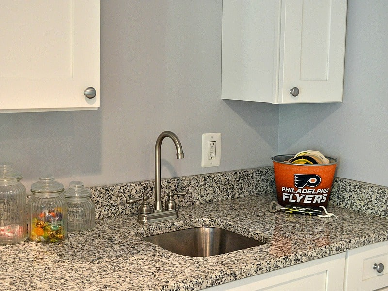 grey speckled counter of wet bar with white cabinets