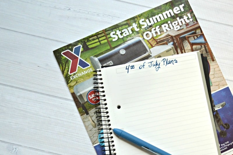 notebook with 4th of July Plans written in blue pen with advertisement paper
