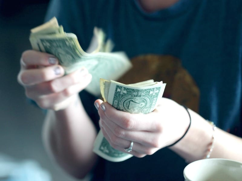 Woman counting $1 bills with cup of coffee