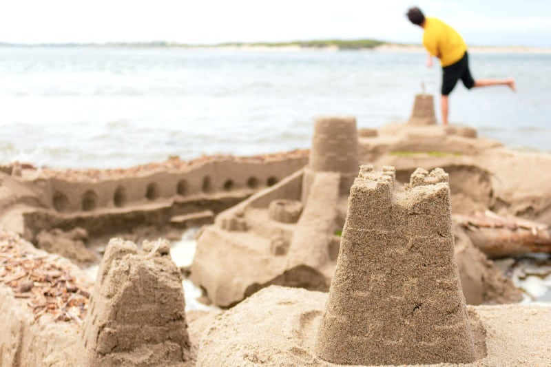 close up of sand castle with man at water's edge in background