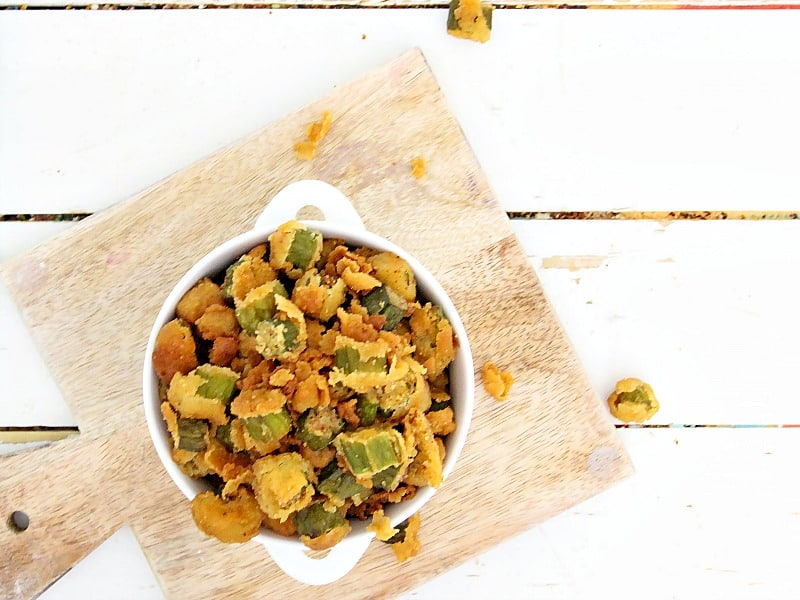 overhead view of fried okra in white bowl on wood cutting board