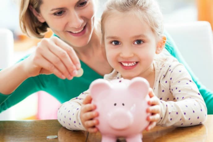 Young girl holding piggy bank with mother putting coin into it