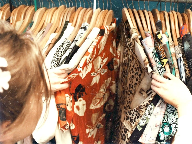 Woman looking through rack of shirts on wood hangers