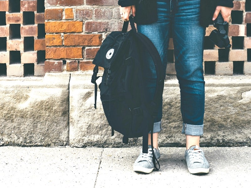 girl in jeans and tennis shoes holding black backpack