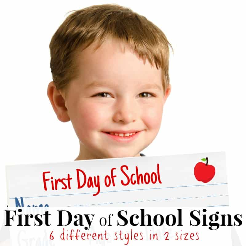Young boy holding first day of school sign and smiling