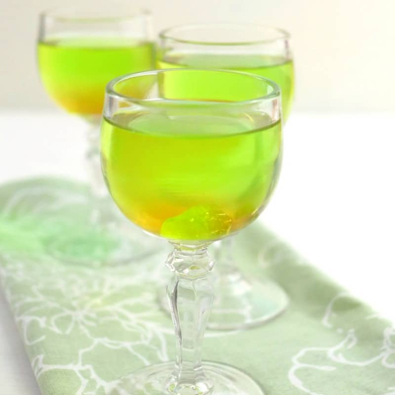 3 glasses with green liquid and green jolly rancher in cup