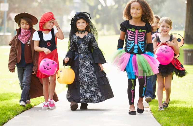 six kids in Halloween costumes walking down the sidewalk