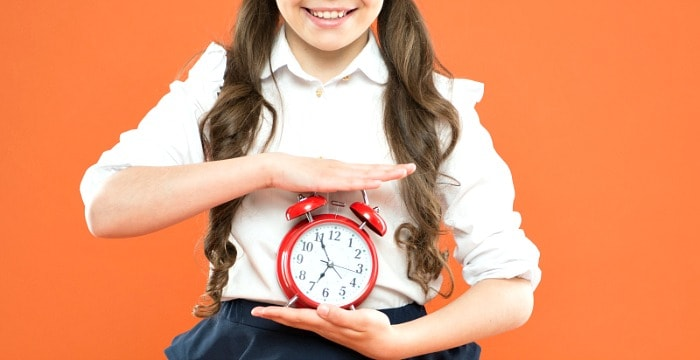 Close up of school girl holding a red alarm clock