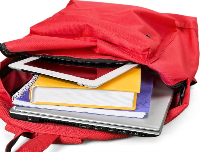 Open red backpack with books and notebooks
