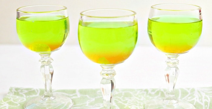 3 Halloween cocktail glasses in a row filled with bright green liquid