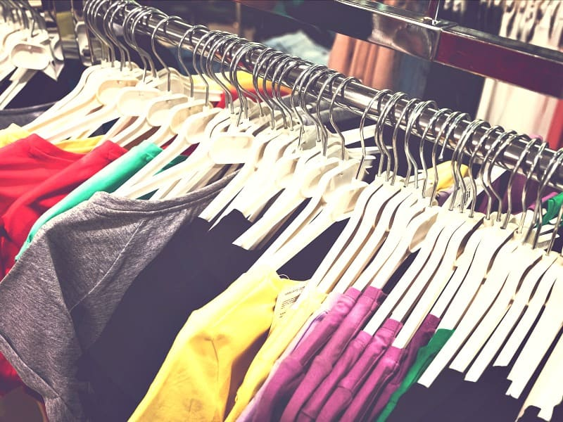 row of brightly colored t-shirts on hangers