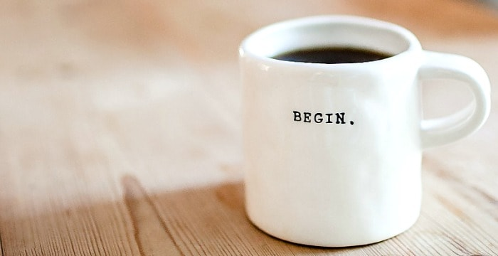 "White cup with black ""begin."" filled with coffee on  wood table"
