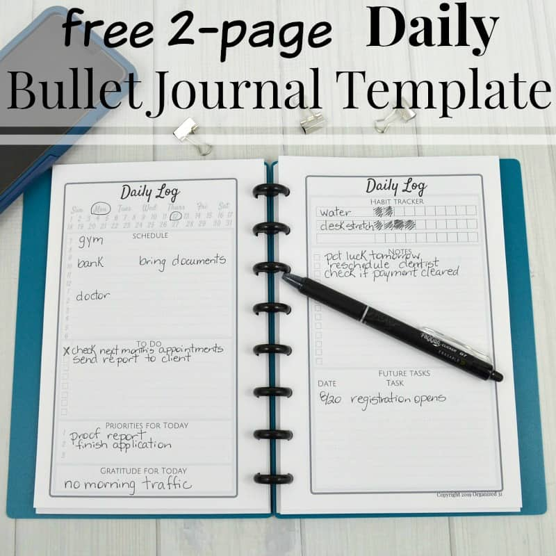 Bullet journal laying open on table with black pen, phone and text overlay