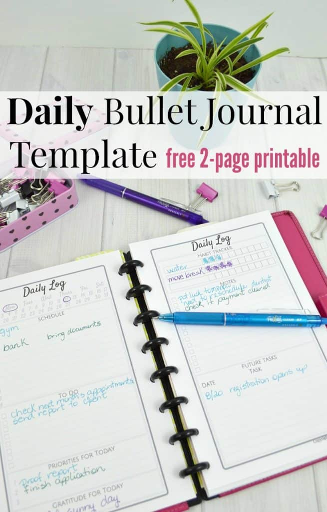 Daily Log in pink bullet journal with colorful pens, paper clips on a desk with a plant and text overlay