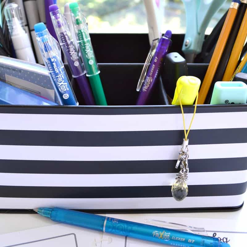 Close up of black and white desk organizer with colorful pens
