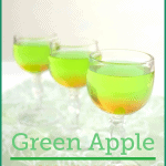 3 wine glasses of green and orange drink on green table cloth
