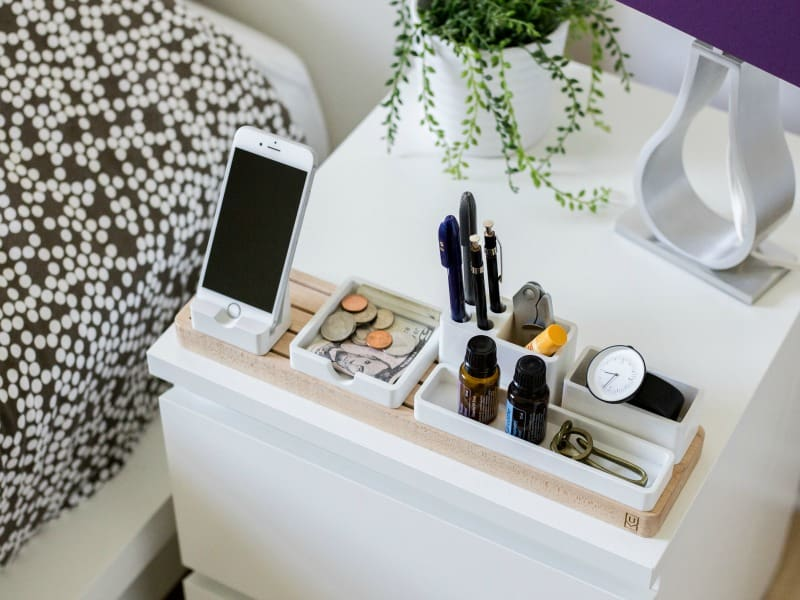 White bedside table with cell phone charging and other organized items.