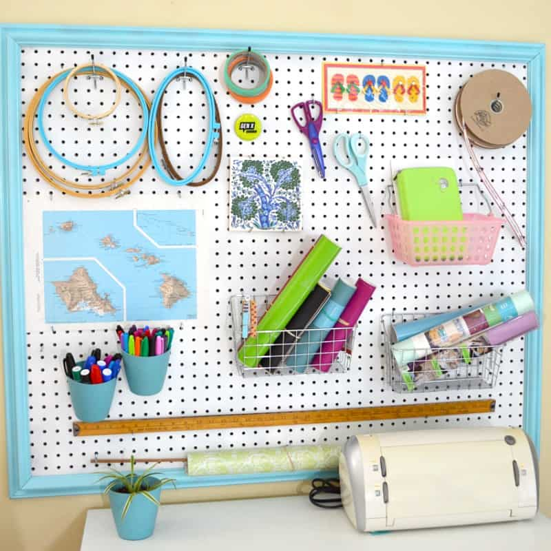 peg board on a wall with several craft supplies hung on it
