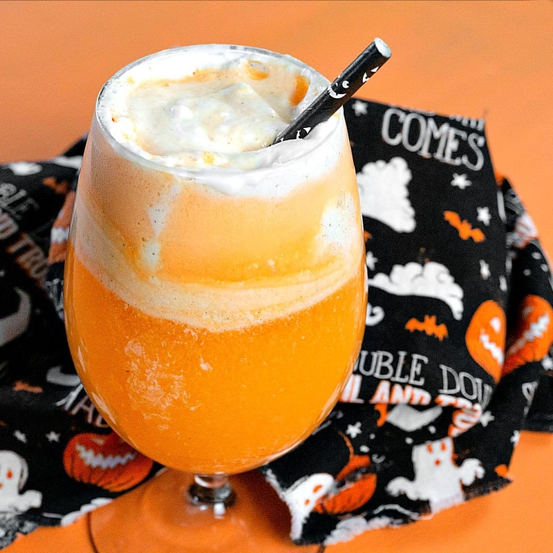 frothy orange drink with black Halloween fabric in background