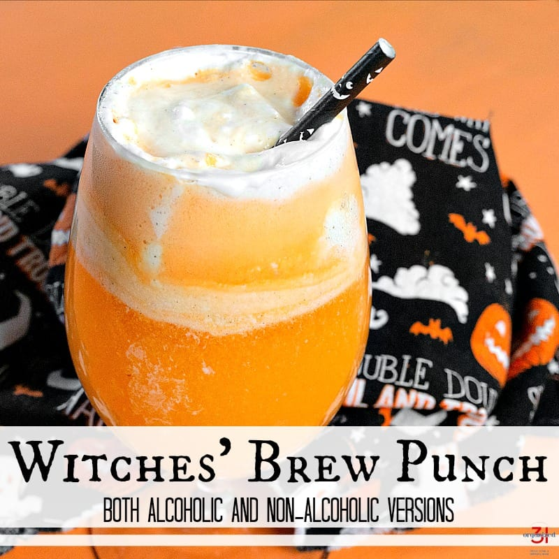close up of orange witches brew in glass with black straw