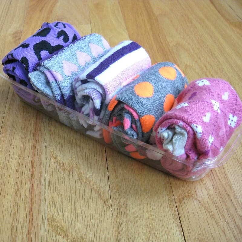 5 brightly colored socks folded and organized in clear container on wood table