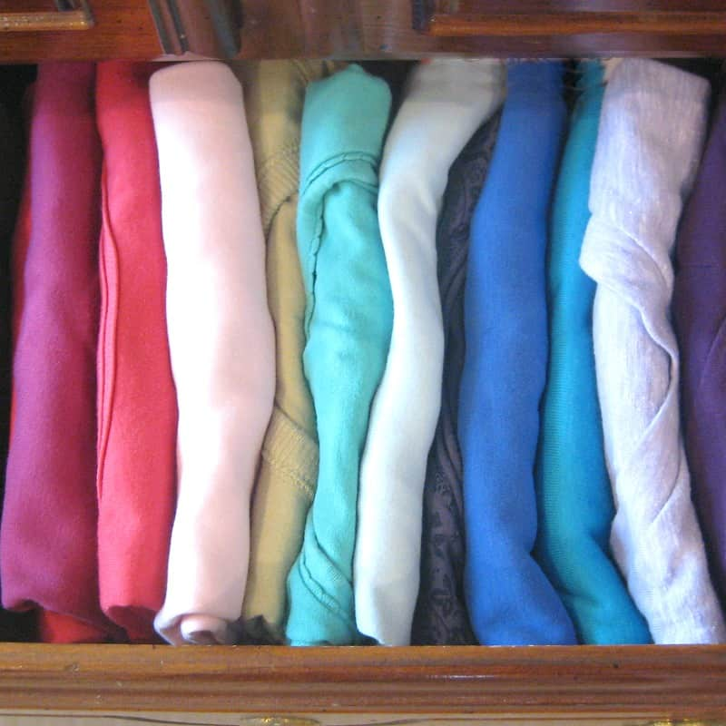 t-shirts neatly folded in drawer and organized by color