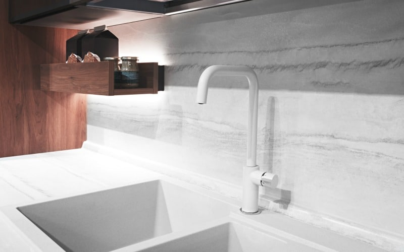 white sink with white and grey marble counter and backsplash
