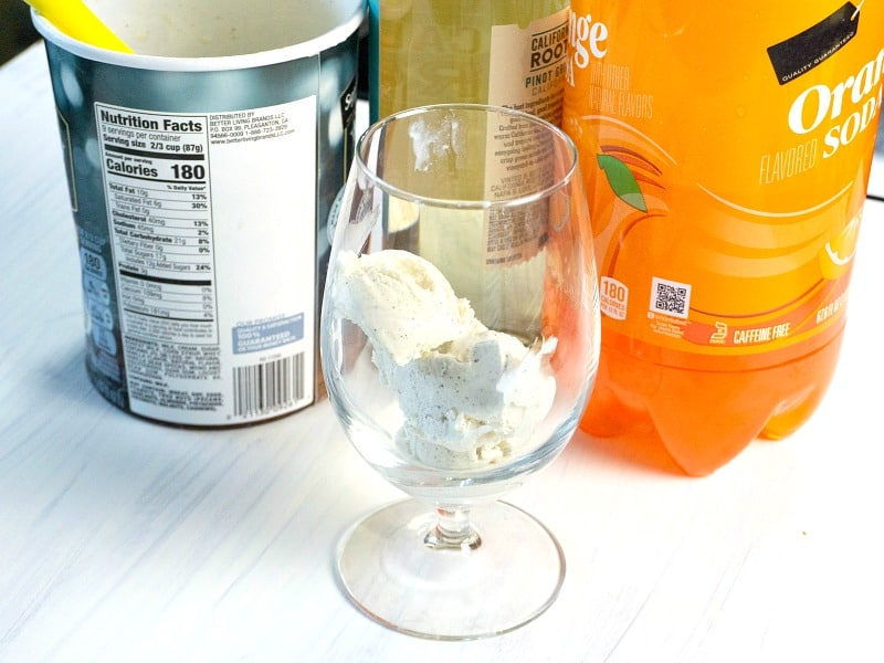 glass with scoop of ice cream in front with container of vanilla ice cream, wine bottle and orange soda in the background