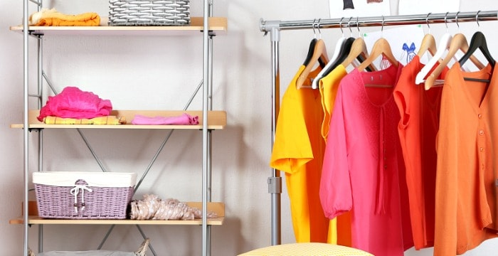 Brightly colored women's clothing hanging on rod and folded on shelves