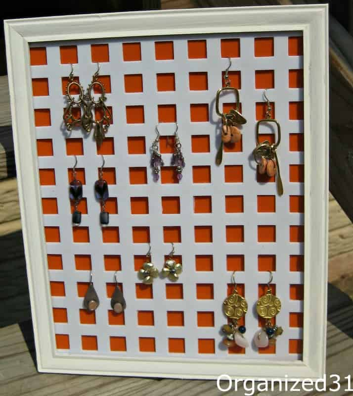 White and orange ear ring organizer on wood table