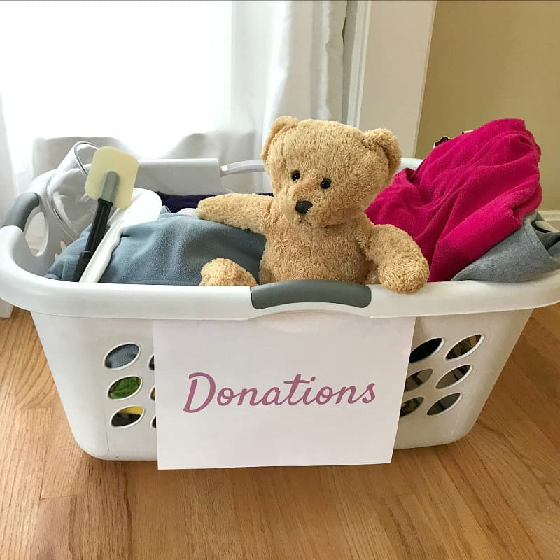 "basket with sign ""donations"" on front with miscellaneous items and a teddy bear"