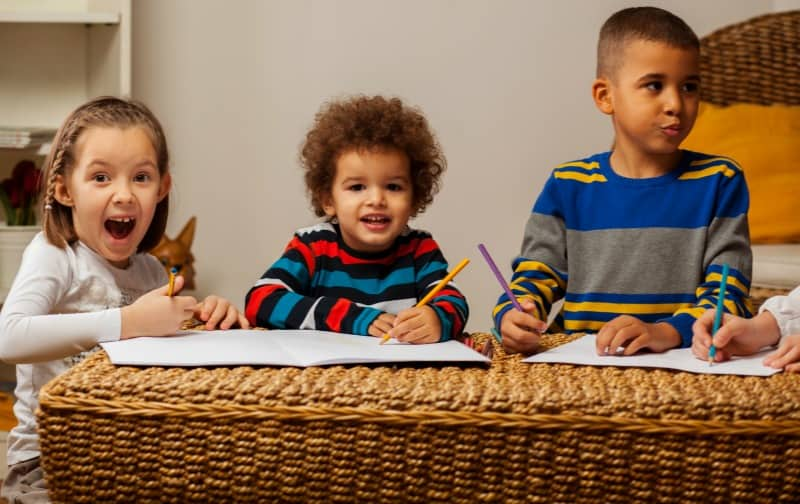 3 children happily writing on paper