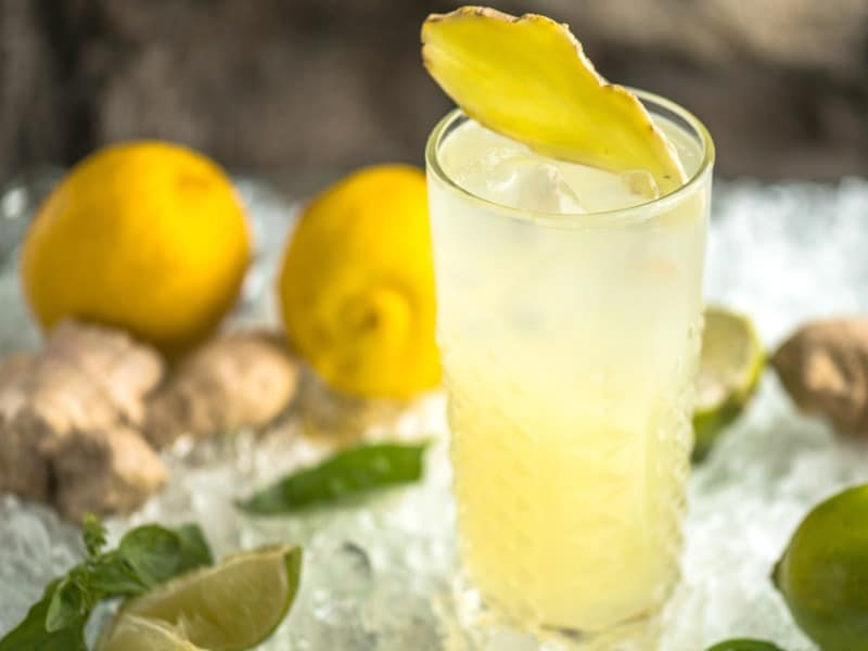 Close up of glass of lemon water with lemons, limes and herbs scattered in the background