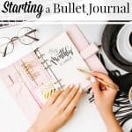 pink bullet journal with woman's hands and glasses