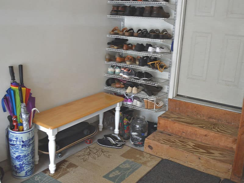 garage door with wall of shelves with shoes, bench and umbrella stand