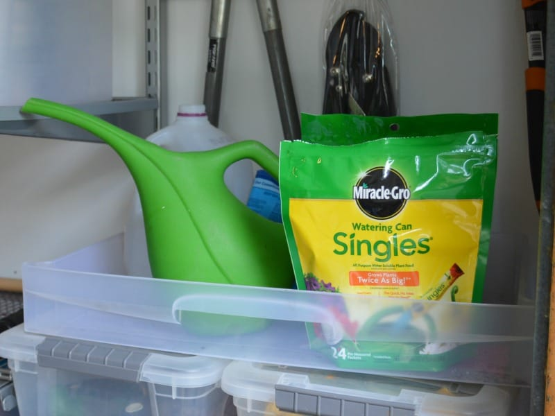 Plastic bin holding green watering can and green and yellow bag of fertilizer