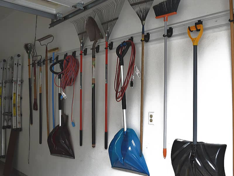 wall of neatly organized yard rakes, shovels and brooms