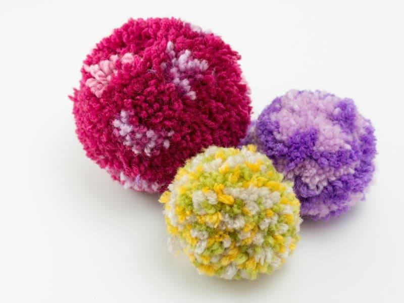 3 colorful yarn pom poms