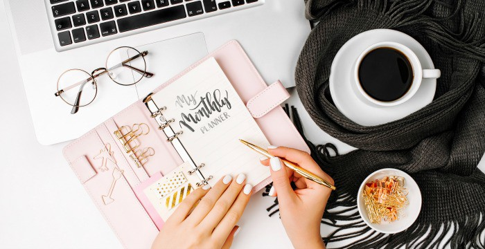 woman using pink bullet journal with laptop, glasses and cup of coffee