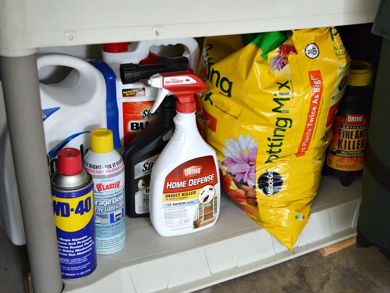 Chemicals in bottles and a yellow bag on bottom garage shelf