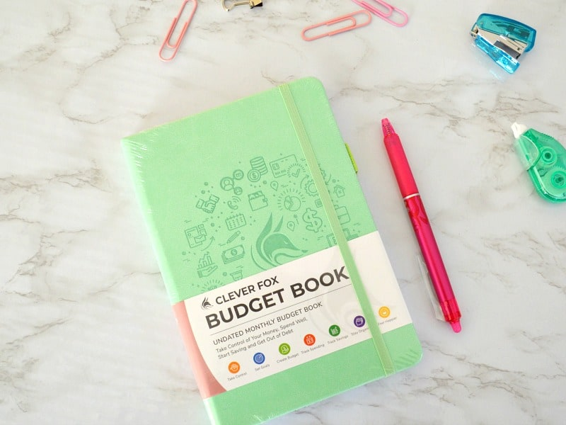 green Clever Fox budget book on marble table top with pens, paper clips and stapler