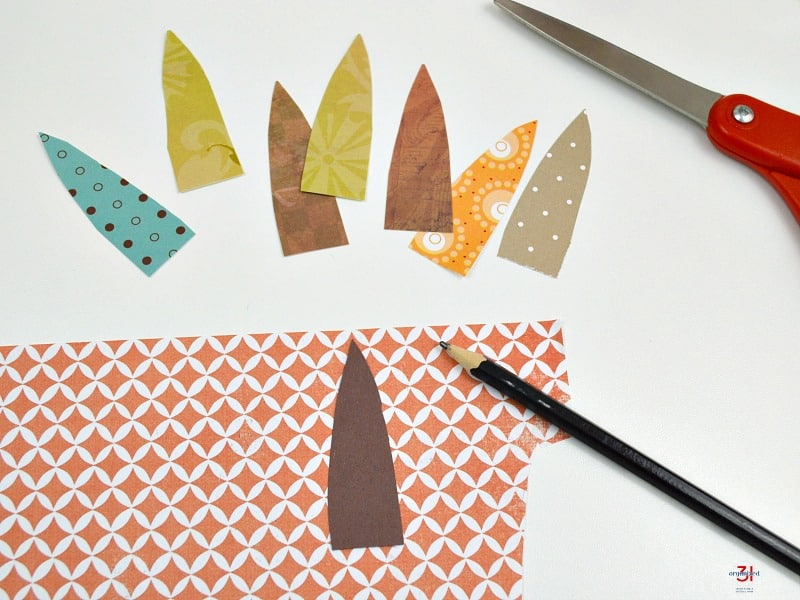 colorful turkey tail feathers cut out of paper with pencil and scissors