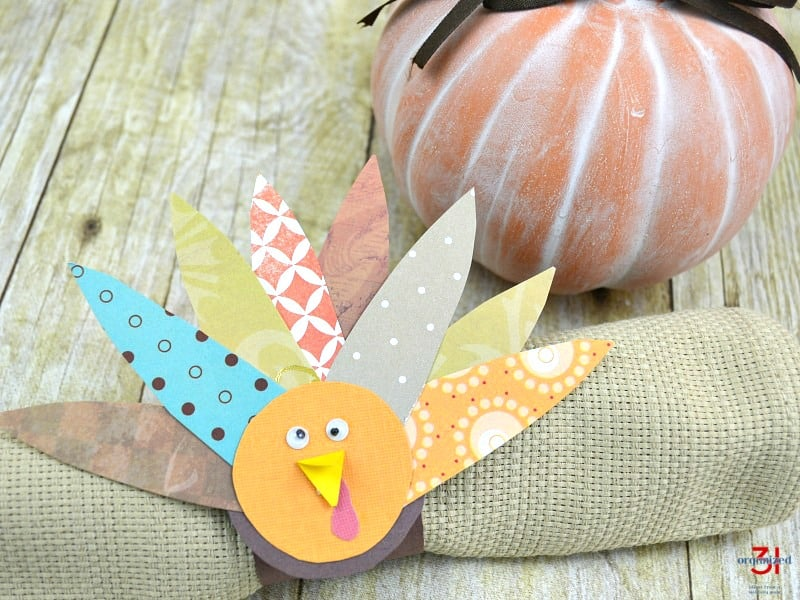 DIY paper turkey napkin ring on tan napkin with terra cotta pumpkin in the background